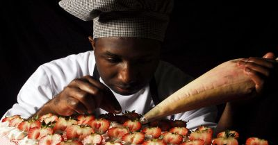chef working in a bakery on a dessert cake with strawberries and frosting