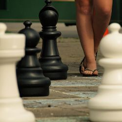 large chess pieces on a giant game board with a persons feet