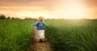 young girl in a hat in a meadow at sunset