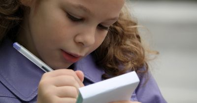 young girl writing a note on a pad of paper with a pen