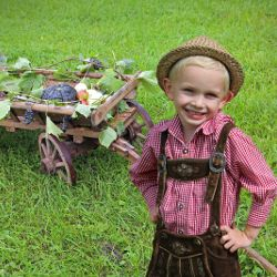 young boy with a harvest of pumpkins in a wagon
