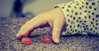 hand of a child reaching out to grab red candies