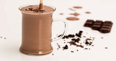 chocolate milk shake surrounded by chocolate sprinkles and a chocolate bar