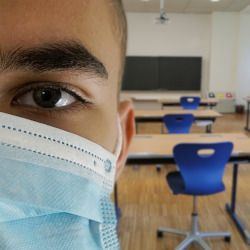 Masked student with classroom in background