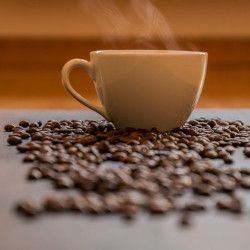 steaming cup of coffee surrounded by roasted coffee beans