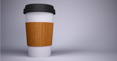 disposable paper coffee cup with a brown sleeve and black lid