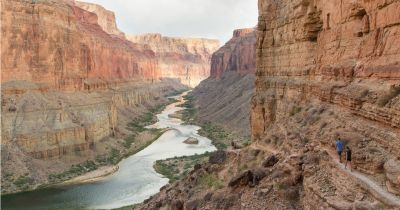 two hikers walking along a canyon path near the Colorado River on a sunny day