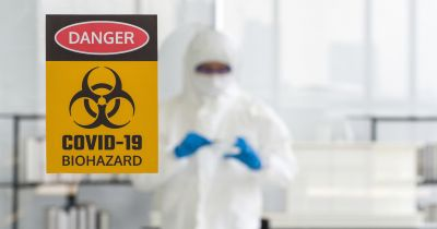 person in a biohazard suit researching a virus in a petri dish in front of a biohazard sign