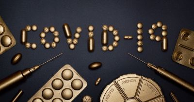 COVID 19 spelled out with golden colored pills and capsules