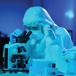 scientist in a hazmat suit in a laboratory doing research at a microscope