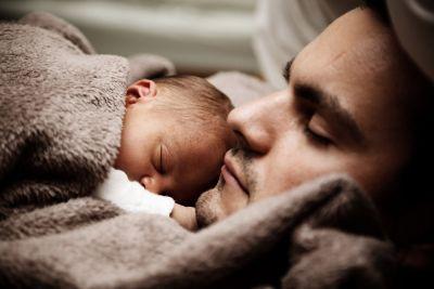 Father and newborn sleeping peacefully