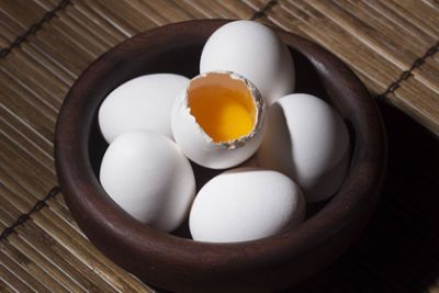 Several eggs in a bowl with one cracked open