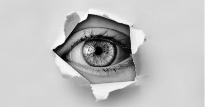 A single eye spying through a torn hole in some paper