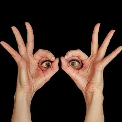 Woman holding her fingers around her eyes against a black background