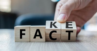 Hand rotating small wooden blocks between spelling Fake and Fact