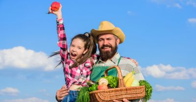 father and daughter farmers in a farm field triumphantly holding up their harvest