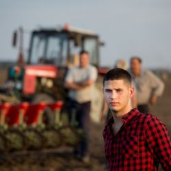 farmers standing next to a tractor in a farm field