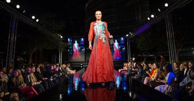 model dressed in a red gown walking down a runway at a fashion show