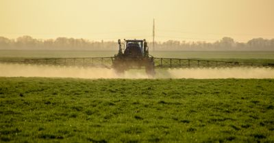 tractor on a farm spraying liquid chemical fertilizer on a crop field at sunset