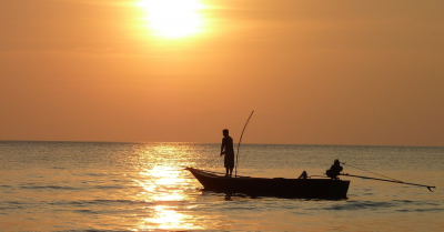 Fisherman fishing in a boat at dusk