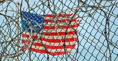 tattered American flag behind a chain link fence and razor wire