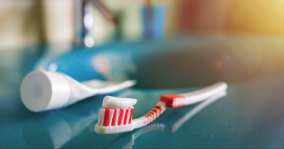 Toothbrush with toothpaste on it sitting next to toothpaste tube.