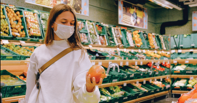 Masked woman shopping for food, holding a grapefruit.