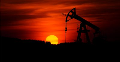 silhouette of an oil rig fracking into the earth at sunset