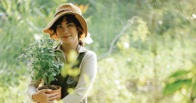 A woman holding a potted plant.