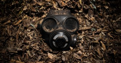 gas mask on the forest floor surrounded by dead leaves