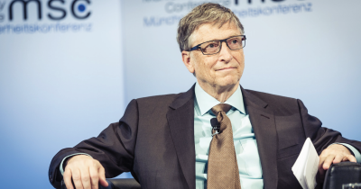 Photograph of Bill Gates sitting in a chair in a suit with a blue background