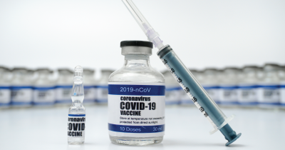 A photograph of a covid-19 vaccine in a bottle with an injection needle leaning on it.