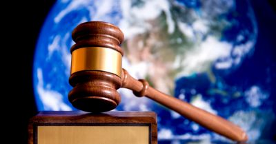 gavel with image of earth behind it