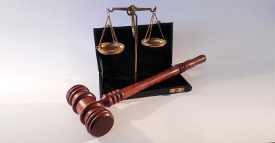 scales of justice in a black briefcase with a judges gavel
