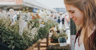 woman standing at a farmers market stall
