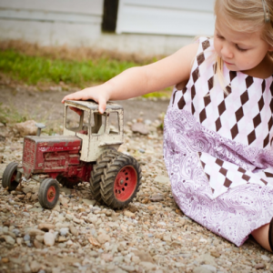 Girl playing with a toy tractor