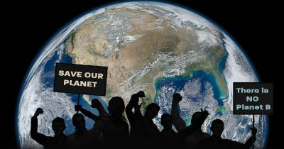 silhouette of protesters at a march for climate change over a space view of the planet earth