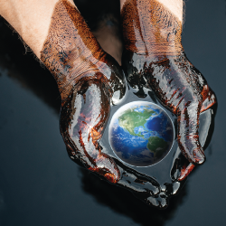 Hands covered in oil holding the earth.