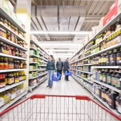 view of a shopping card moving down a grocery store aisle with customers