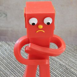 Red toy figure with a sad face holding its belly