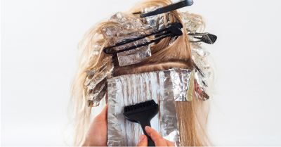 hairdresser in a salon coloring a womans hair with foil and a brush