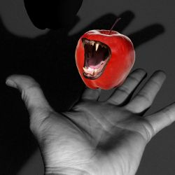 persons hand holding a red apple that is bearing sharp monster teeth