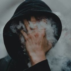 person holding their hand over their hooded face with smoke circling