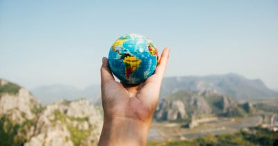 hand holding a small world globe against a mountain landscape