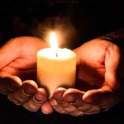 hands holding a white candle alight with a flame