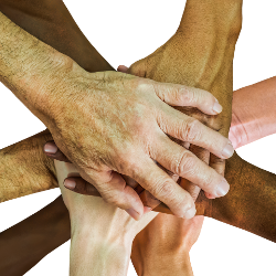 Many people holding their hands together in teamwork