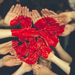 hands coming together with red paint in the shape of a heart