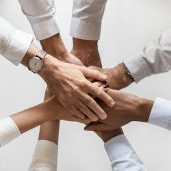 several business people with their hands held together in a huddle