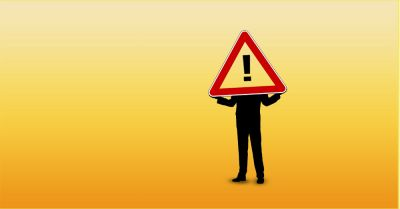 silhouette of a man holding a hazard sign with an exclamation point