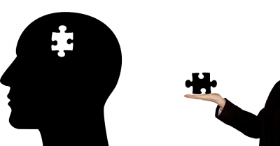 silhouette of a head with a puzzle piece taken out of it